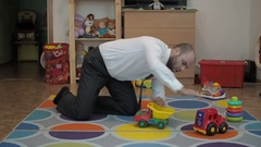 Adult male businessman playing toy cars sitting on the floor in the nursery. Stock Footage