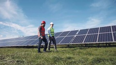 Workers walking in between rows of solar panels Stock Footage