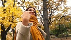 Happy, pretty woman correcting scarf while walking in autumn park, super slow mo Stock Footage