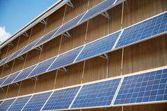 Solar battery panels on building facade Stock Photos