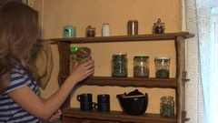 Peasant woman smell chamomile herbs in jar and smile. Static shot. 4K Stock Footage