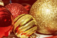 Red and yellow shimmering christmas baubles, retro photo filter Stock Photos