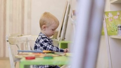 Boy sitting on a chair in front of his easel in drawing school. Stock Footage