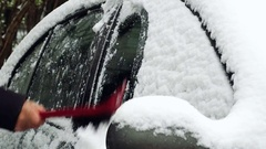 Cleaning windows of a car from the snow with a brush Stock Footage