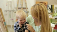 A young mother draws paint her child's face. Stock Footage