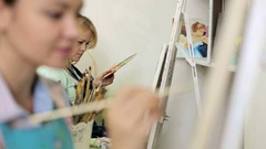 Two beautiful girls paint a picture in art Studio. Stock Footage