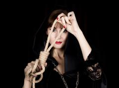 Mysterious young woman holding loop of the rope. on a dark background Stock Photos