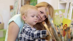 The cute child selects a brush for painting.  Mother and son drawing together. Stock Footage