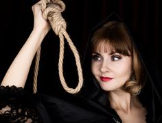 Mysterious young woman holding loop of the rope. on a dark background Kuvituskuvat