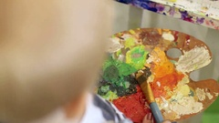 Little boy holding a paint palette. Kid drawing paints. Stock Footage