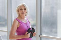 Ambition smiling woman exercising near the window Stock Photos
