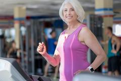 Joyful smiling senior woman exercising on treadmill Stock Photos