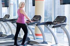 Charming delighted senior woman training on treadmill Stock Photos