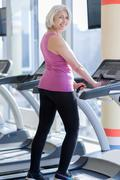 Cute delighted senior woman exercising on treadmill Stock Photos
