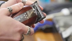 Hands of a man with a vintage barber electric clippers for beard and hair Stock Footage