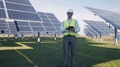 Solar panel technician using tablet near array Stock Footage