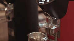 Behind the cafe bar coffee grinder pours ground coffee in holder, female Stock Footage