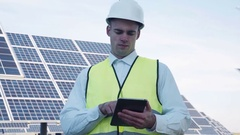 Solar panel technician using tablet near array Stock Footage