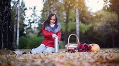 Young woman sitting has picnic drinking hot tea from a thermos in autumn park Stock Footage