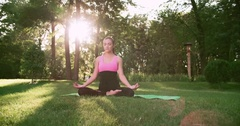 Young beautiful Asian girl doing yoga in the Park in the Lotus position, Dolly Stock Footage
