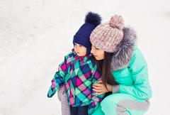 Happy mother holding baby girl on the walk in winter snowy forest Stock Photos