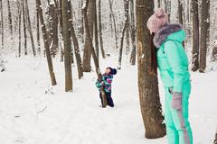 Mother and little toddler girl walking in the winter forest and having fun with Stock Photos