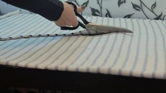 The seamstress cut fabric with scissors Stock Footage