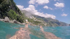 Pov of feet floating in ocean swimming in Amalfi on travel vacation adventure Stock Footage