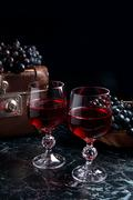 Two glass of red wine on dark marble background. Blue ripe grapes on dark mar Stock Photos