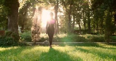 Young beautiful Asian girl doing yoga in the Park starts exercising, the glare Stock Footage