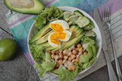 Healthy salad in a bowl. avocado, chickpeas, cucumber and egg. Stock Photos