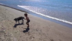 Kid plays with a dog at the lonely beach Stock Footage
