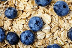 Raw oat flakes with blueberries and mint in white bowl Stock Photos