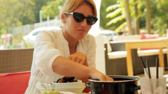 Woman eating mussels at the beach restaurant Stock Footage
