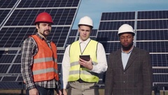 Trio of solar panel engineers outside Stock Footage