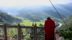 Bhutan monk on top of a monastery with view over Punakha area Stock Footage