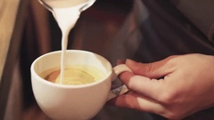 Barista pouring coffee with milk to make art latte. Barista prepares latte in Stock Footage