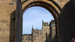 Great Britain England Alnwick Castle buildings behind arc of entrance gate Stock Footage