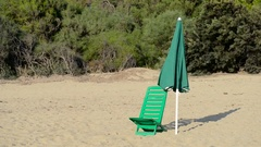 Beach chair and umbrella blows in the wind Stock Footage