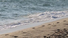 Beautiful powerful waves splashing over golden shore with footprints Stock Footage