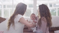 4K New mother with friend or family member holding crying baby daughter at home. Stock Footage
