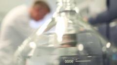 Lab Technician Working Behind Glass Beaker Stock Footage