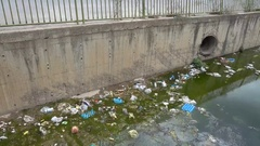 Garbage and green water in drainage ditch Stock Footage