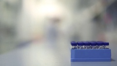 Lab Technicians Moving Behind Block of Vials Stock Footage