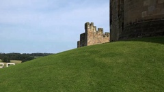 Great Britain England Northumberland part of Alnwick Castle behind green hill Stock Footage