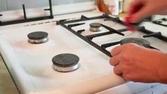 Woman washes a gas stove cleaning in the kitchen Stock Footage