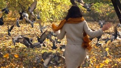 Woman running and scaring pigeons in autumn park, super slow motion 240fps Stock Footage