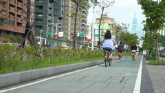 4K people ride bicycles by the street on bike way lane pavement Taipei city -Dan Stock Footage