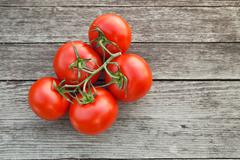 Dewy red tomatoes on the rustic wood Stock Photos