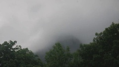Fog swirl, twirl, and envelope a town in Oberammergau, Germany Stock Footage